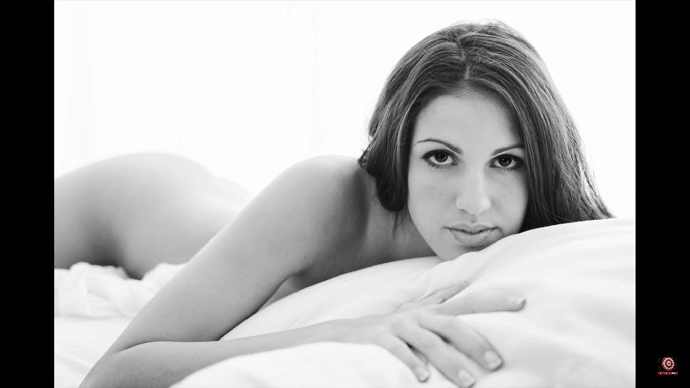 Boudoir shot of model on creme comforter