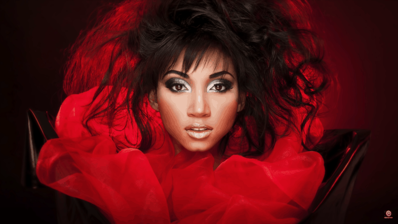 model with red tulle surrounding her and messy hair and silver makeup