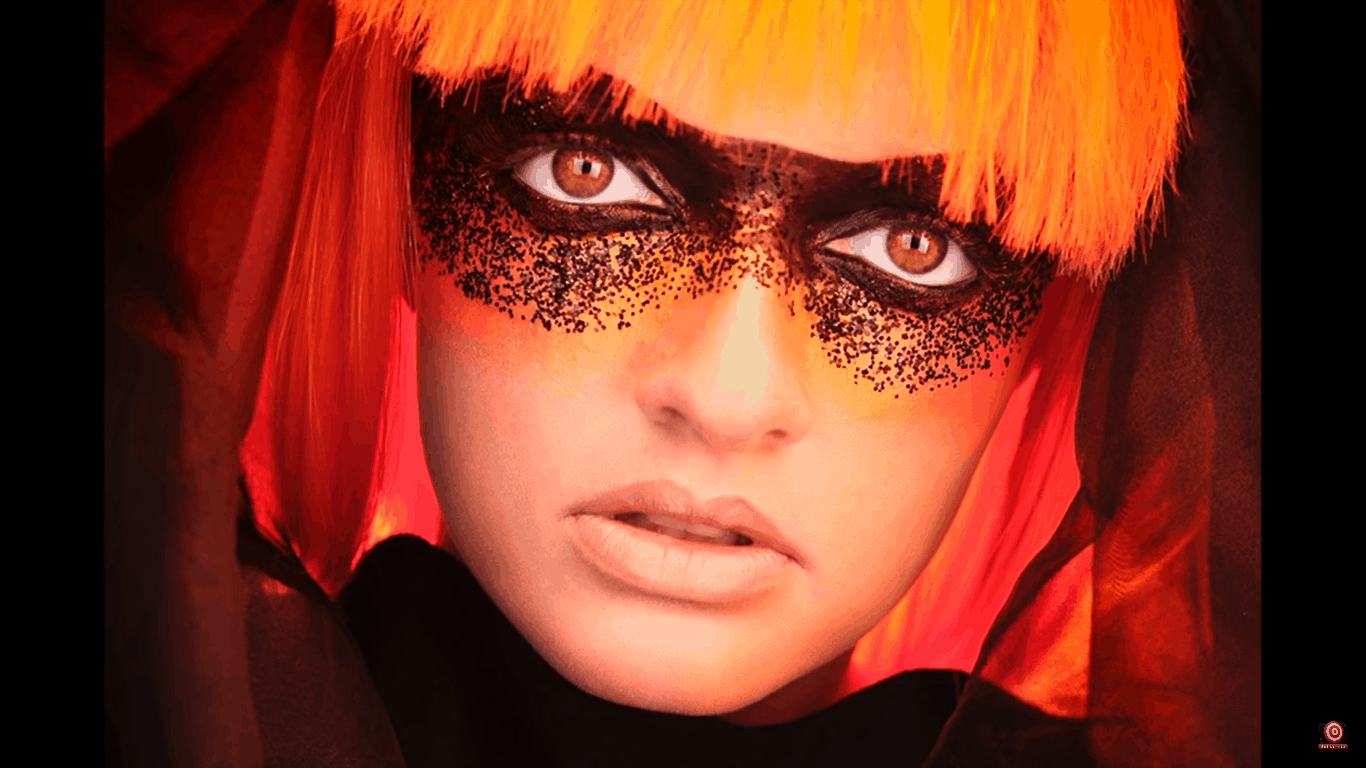 Closeup of model in orange wig with tulle around her lit from behind