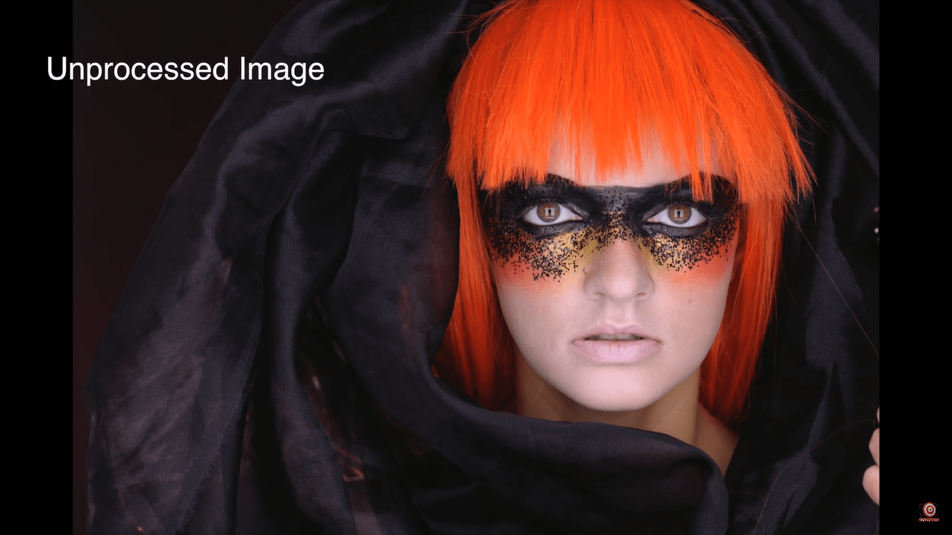model in orange wig with black fabric wrapped around her (unprocessed image)