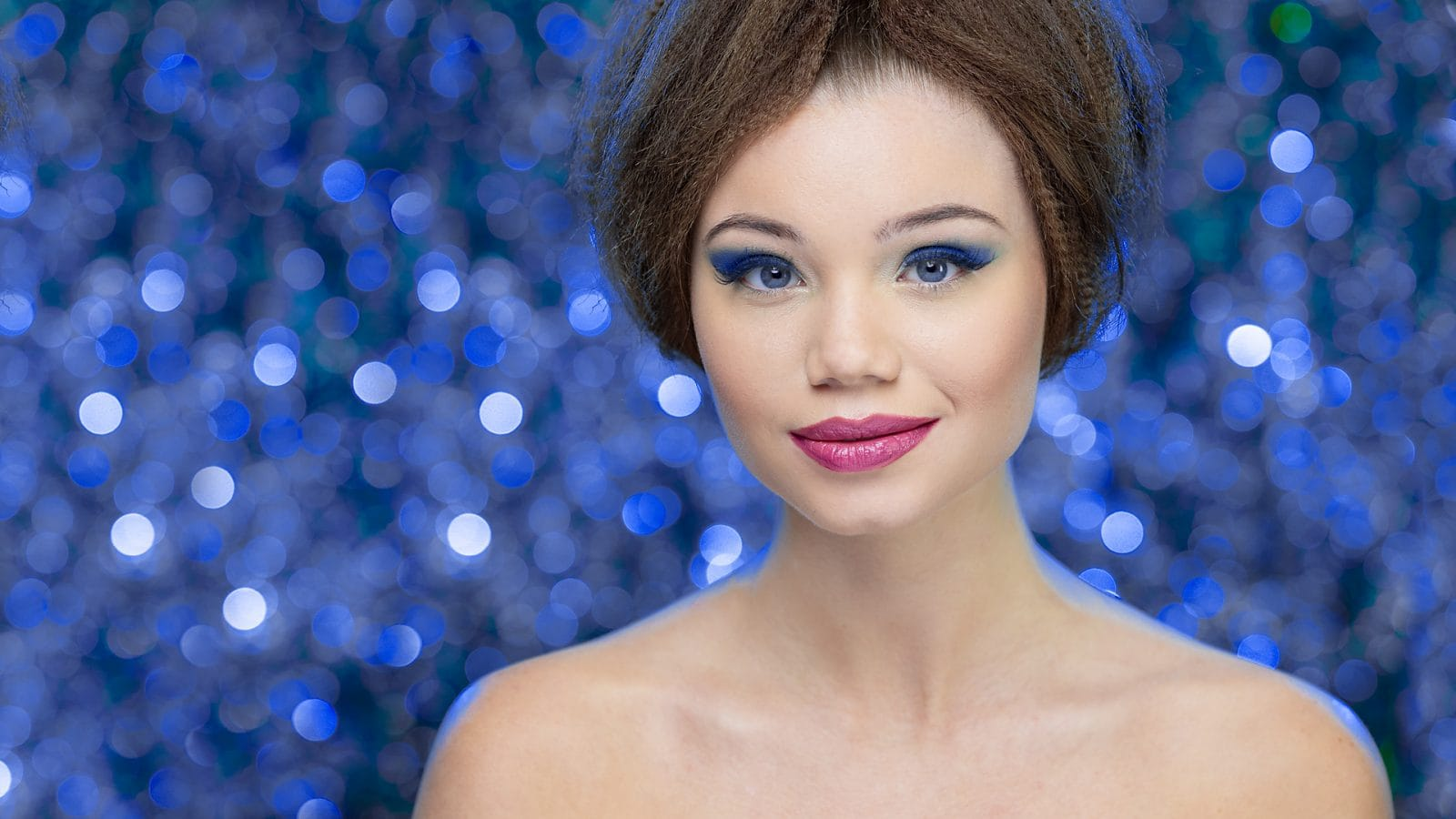 Model in front of blue bokeh background with bare shoulders
