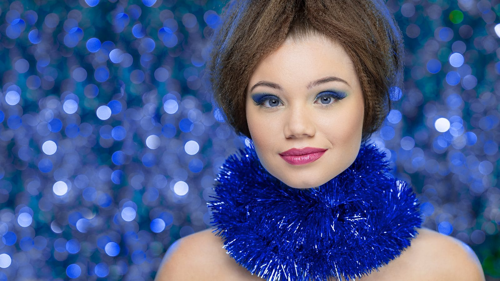 Model in front of blue bokeh background with garland around neck