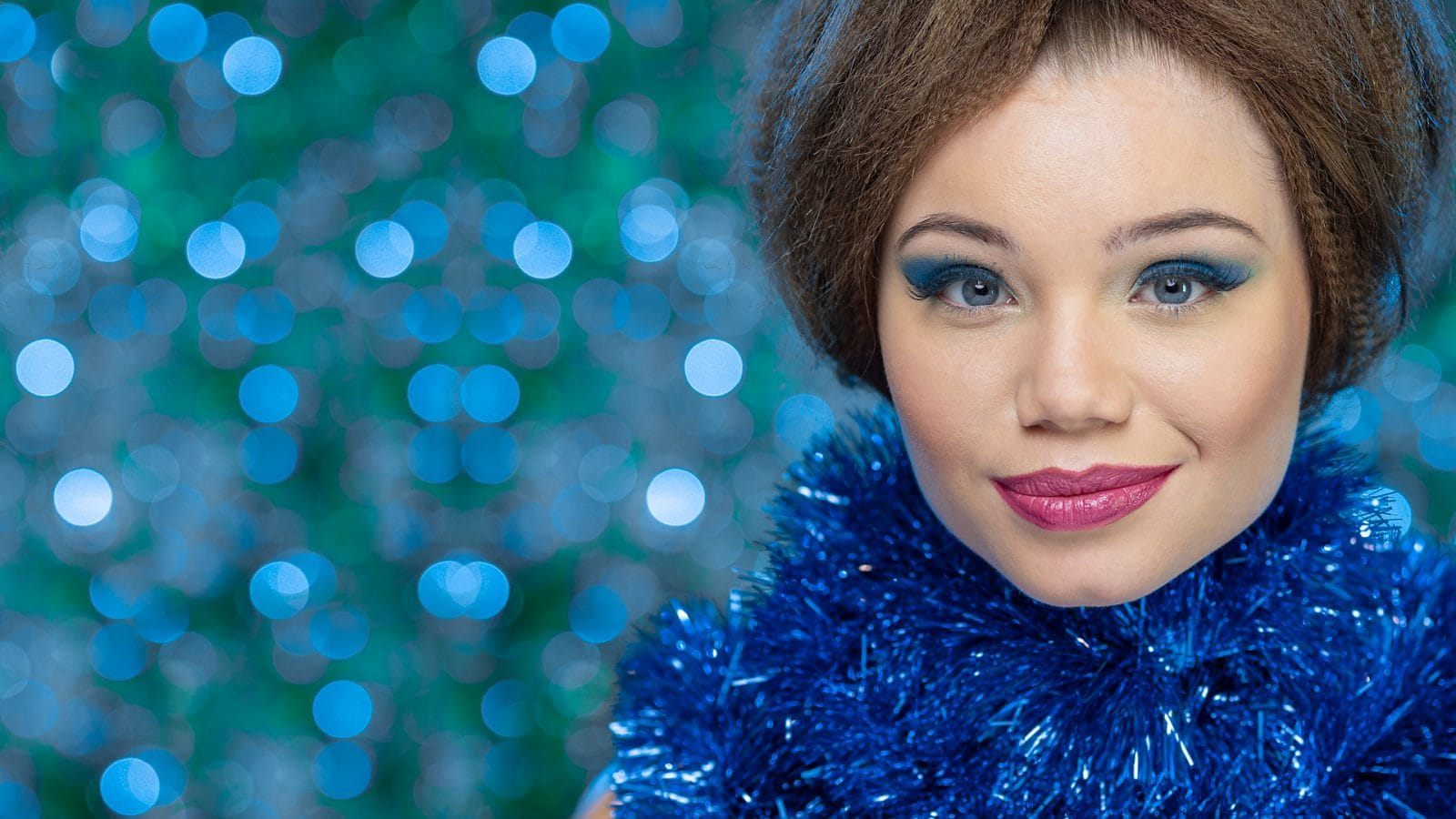 Close up of model in front of blue bokeh background with garland around neck